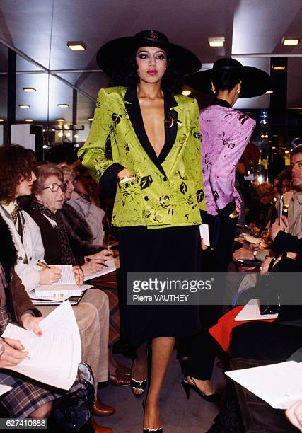 A fashion model wears a vneck haute couture blazer and skirt with a wide brimmed hat by French fashion designer JeanLouis Scherrer She modeled the...