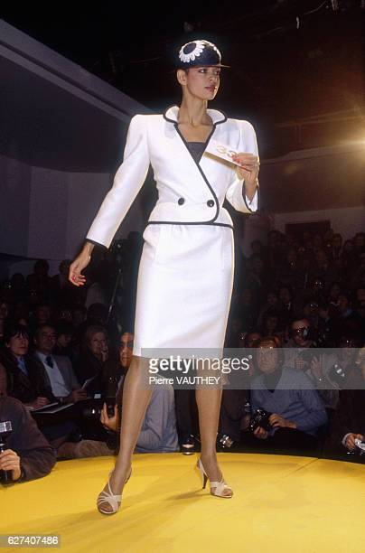 A fashion model wears a white haute couture blazer and skirt by French fashion designer Pierre Cardin She modeled the suit during his springsummer...