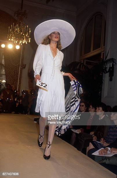 Fashion model wears a white haute couture dress and wide brimmed hat by French fashion designer Marc Bohan for French fashion house Christian Dior....