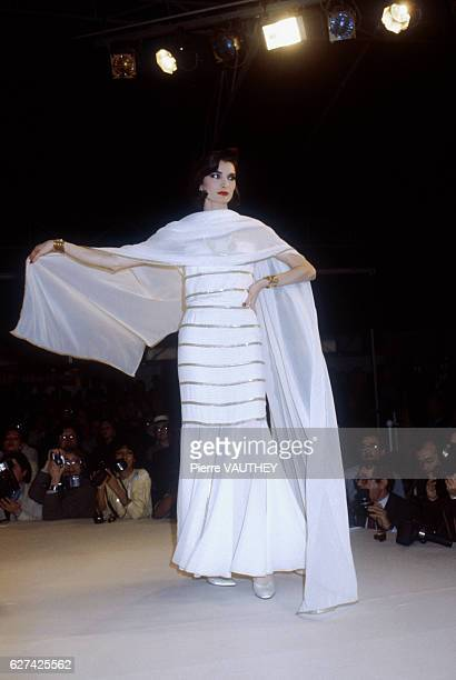 A fashion model wears a white haute couture evening gown with a wrap by German fashion designer Karl Lagerfeld for French fashion house Chanel She...