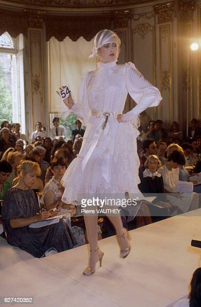 A fashion model wears a white lace haute couture cocktail dress by French fashion designer Emanuel Ungaro She modeled the dress during his...
