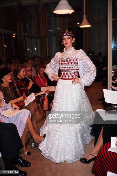 A fashion model wears a white lace haute couture evening gown by German designer Karl Lagerfeld for the French fashion house Chanel during the 1977...