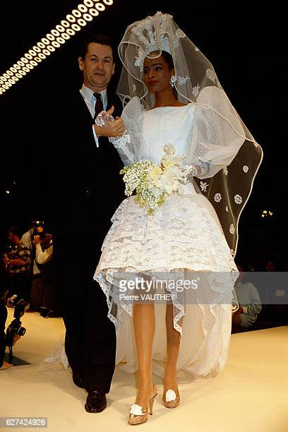 A fashion model wears a white wedding dress with a mantilla and veil by French fashion designer JeanLouis Scherrer at his springsummer 1987 fashion...