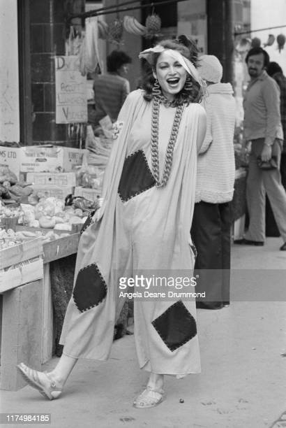 A fashion model wears a wide jumpsuit with patch inserts an oversize chain necklace and jelly shoes as she walks through a street market UK 18th...
