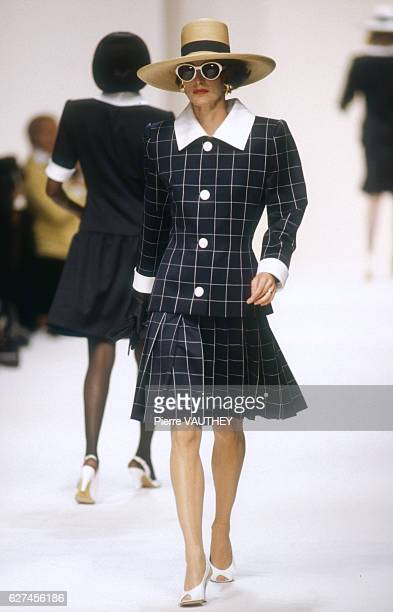 A fashion model wears a women's readytowear black plaid suit with brimmed hat by French fashion designer Givenchy at his SpringSummer 1992 fashion...
