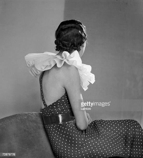 A fashion model wears an evening gown designed by French fashion designer Jeanne Lanvin which has a large ruffled neckpiece Paris March 1934