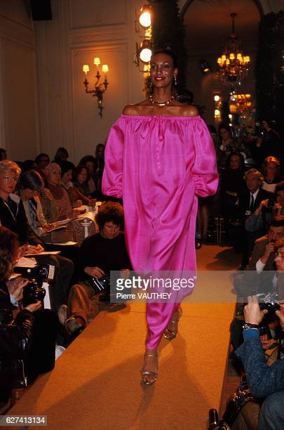 A fashion model wears an offtheshoulder magenta haute couture cocktail dress by French fashion designer Marc Bohan for the Christian Dior fashion...