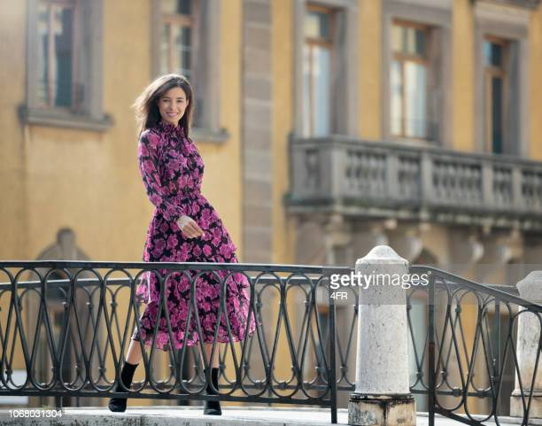 fashion model with a candid smile on a bridge in venice, italy - dress stock pictures, royalty-free photos & images