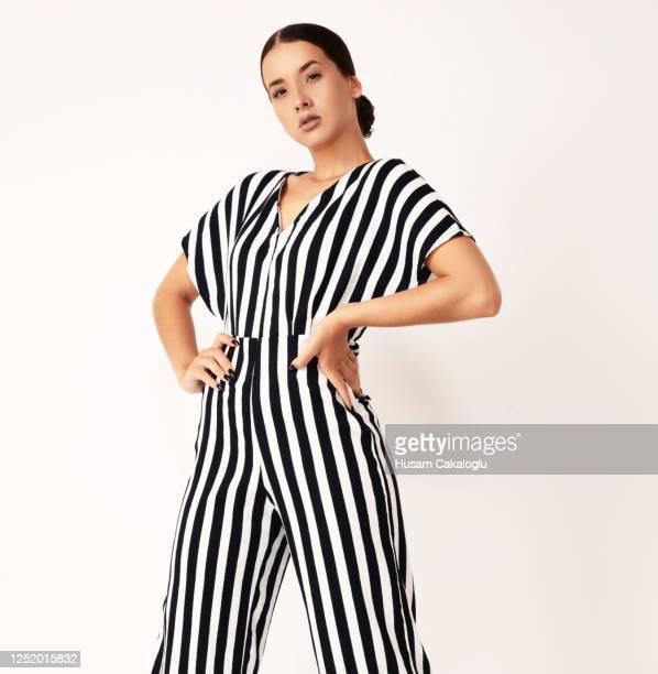 fashion model young woman standing with striped full body dress front of white background. - só uma mulher jovem imagens e fotografias de stock