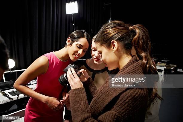 Fashion models backstage looking at digital photos