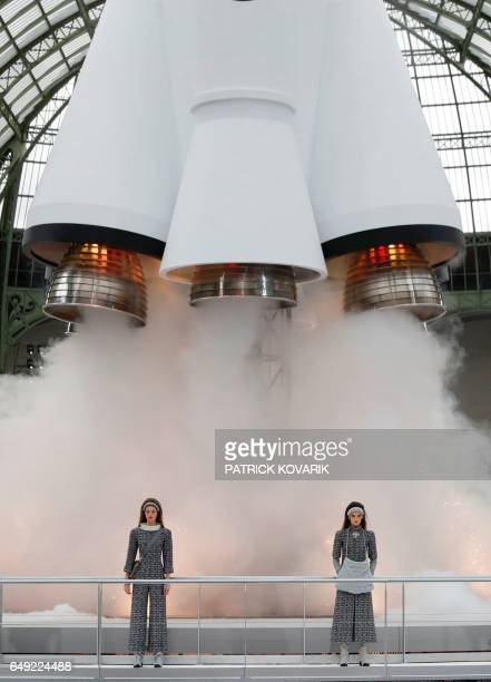 Fashion models stand in front of a replica of a space rocket launch during the Chanel women's FallWinter 20172018 readytowear collection at the Grand...