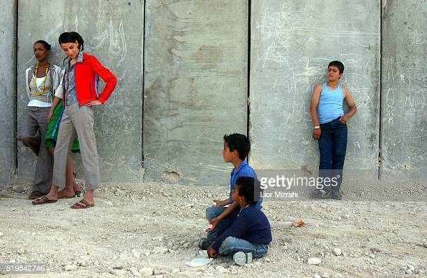 Fashion models take a break from their fashion shoot being done by the controversial Israeli separation wall in ATur in Arab East Jerusalem as...