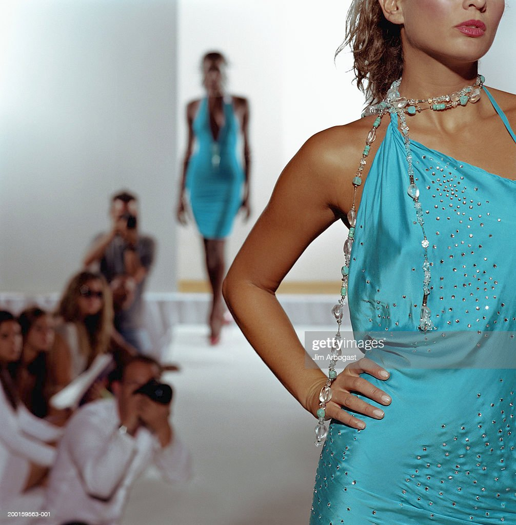 Fashion models walking on catwalk (focus on woman in foreground) : Stock Photo