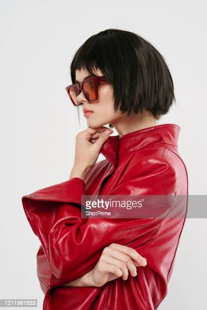 fashion photo of a young woman who propped her head on her hand and thought black hair hairstyle bargain large orange glasses red jacket. - fashion designer stock pictures, royalty-free photos & images