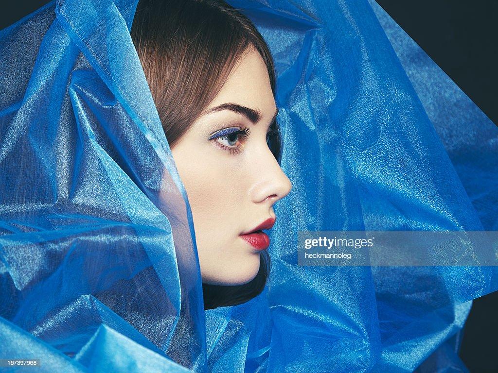 Fashion photo of beautiful women under blue veil : Stock Photo