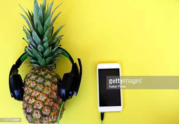 Fashion pineapple with sunglasses, mobile phone and headphones over yellow background