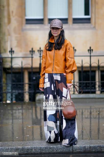 Fashion Pornwika wears a Burberry cap monogram hat, a brown/orange leather jacket, a pleated skirt with printed patterns, a brown leather bag shaped...