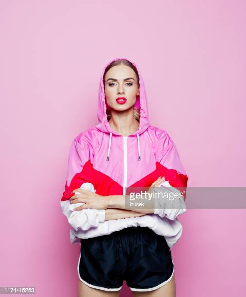 fashion portrait of beautiful woman in tracksuit against pink background - design stock pictures, royalty-free photos & images