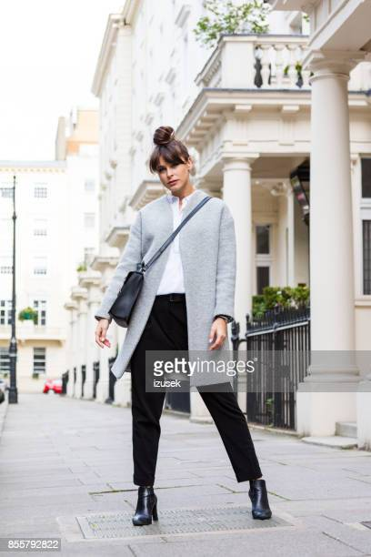 fashion portrait of elegant beautiful woman standing in the city street - gray coat stock pictures, royalty-free photos & images