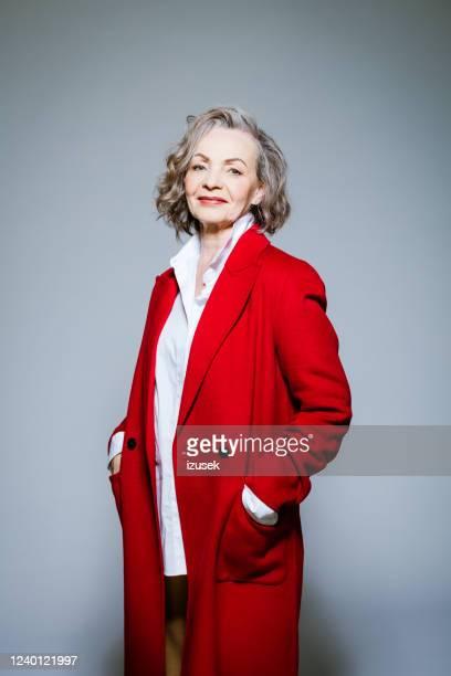 het portret van de manier van elegante hogere vrouw die rode laag draagt - izusek stockfoto's en -beelden