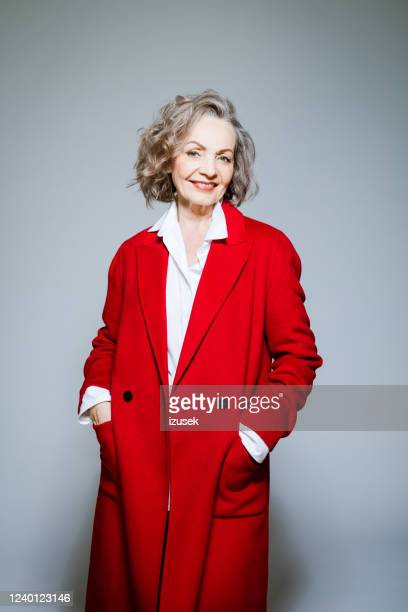 fashion portrait of elegant senior woman wearing red coat - coat stock pictures, royalty-free photos & images