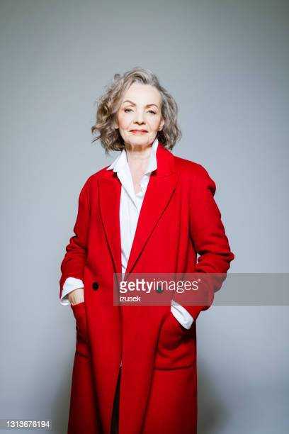 fashion portrait of elegant senior woman wearing red coat - red stock pictures, royalty-free photos & images