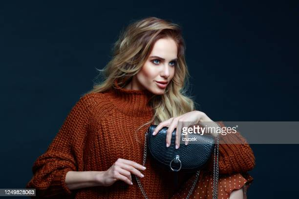 fashion portrait of elegant woman in brown sweater, dark background - clutch bag stock pictures, royalty-free photos & images