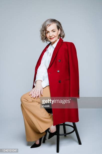 fashion portrait of stylish senior woman wearing red coat - red stock pictures, royalty-free photos & images