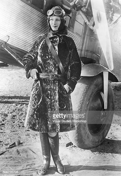 Fashion portrait of woman outside of an airplane sporting a leopard jacket trimmed with leather and a Sam Brown belt early to mid 20th century