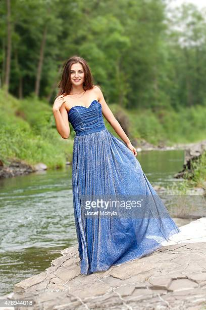 Fashion portrait of young brunette woman standing by river