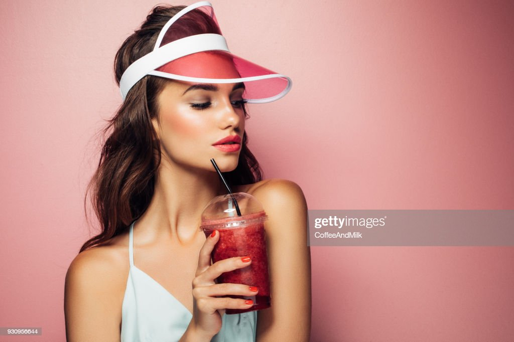 Fashion pretty cool girl drinks from cup over pink background : Stock Photo