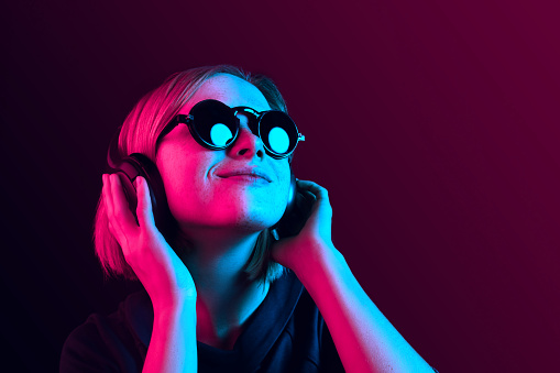 Fashion pretty woman with headphones listening to music over neon background 1131388965