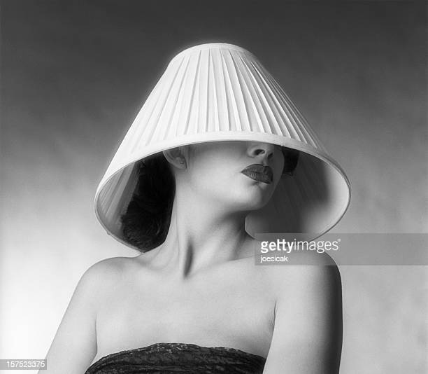 a fashion shot of a woman with a lampshade on her head - ugly lips stock photos and pictures