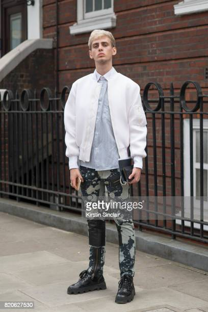 Fashion student and model Nikolas Santur wears Underground shoes KTZ trousers vintage shirt Coach wallet and a CMMN SWDN jacket on day 3 of London...