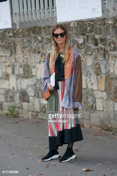 Fashion stylist Blanca Miro Scrimieri wears a Loewe coat and skirt Balenciaga trainers and Saint Laurent sunglasses day 4 of Paris Womens Fashion...