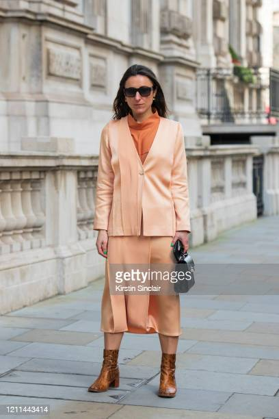 Fashion stylist Laura Parke wears a Judy Wu top jacket and skirt Miista boots and a Picketts bag during London Fashion Week February 2020 on February...