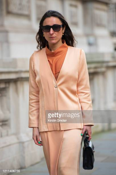 Fashion stylist Laura Parke wears a Judy Wu top jacket and skirt and a Picketts bag during London Fashion Week February 2020 on February 18 2020 in...