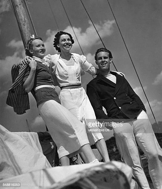 Fashion - summer fashion: two women and a man on a sailboat, the woman on the left wearing a suit in white and red terry cloth and a red-white blazer...