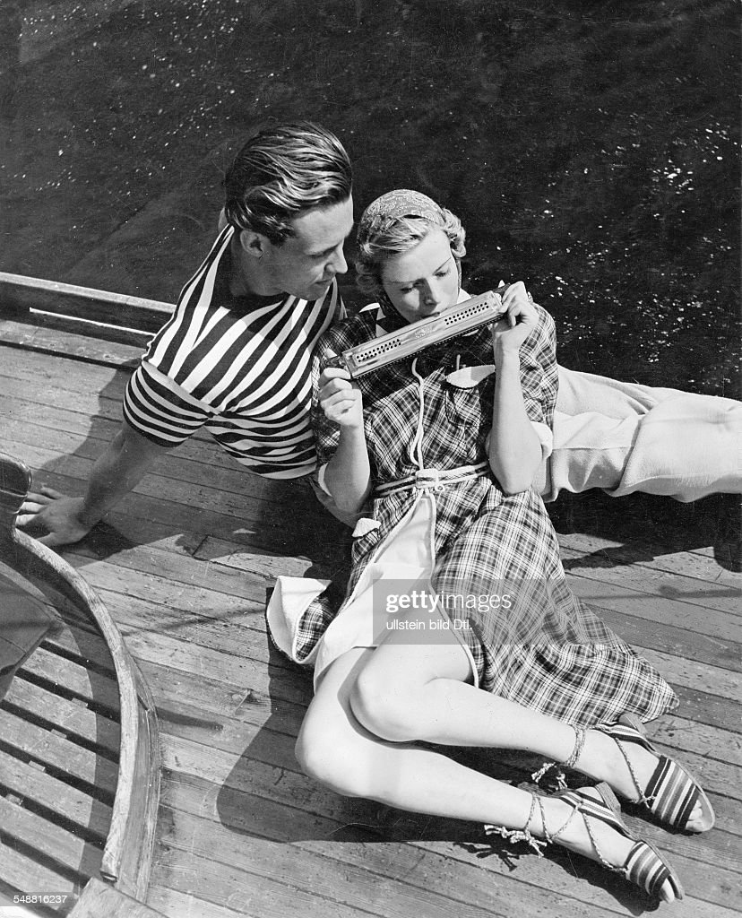 Fashion - summer fashion: woman and man playing harmonica on a sailboat, she wearing a checked linen bathrobe lined with white terry cloth, he wearing a striped short-sleeved jumper and linen pants model: Gerson - 1937 - Photographer: Sonja Georgi -  : Foto di attualità