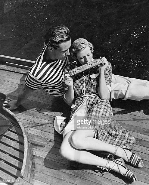 Fashion - summer fashion: woman and man playing harmonica on a sailboat, she wearing a checked linen bathrobe lined with white terry cloth, he...
