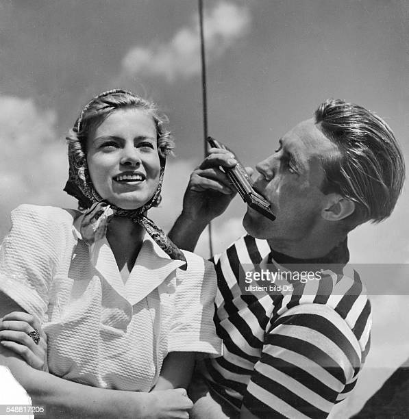 Fashion - summer fashion: young woman with a headscarf in a white pique suit and the man in a striped sweater with harmonica models: Steinhardt -...