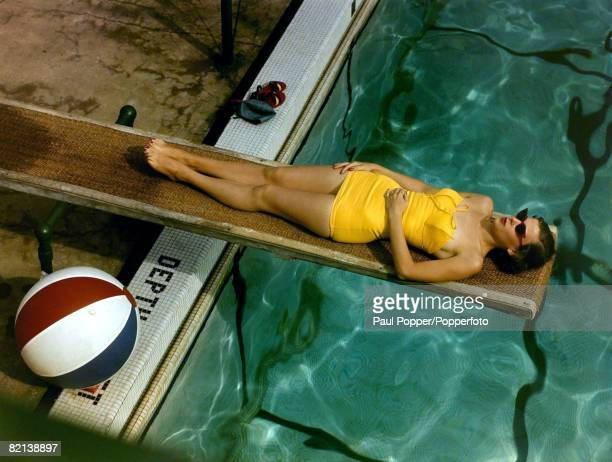 circa 1950's Woman wearing yellow swimsuit relaxing at the poolside