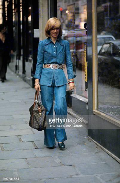 Fashion The Blue Jeans France 1973 L'empire du bluejeanUne jeune femme vêtue d'un ensemble jean longue chemise à boutons sur un bluejeans évasé...