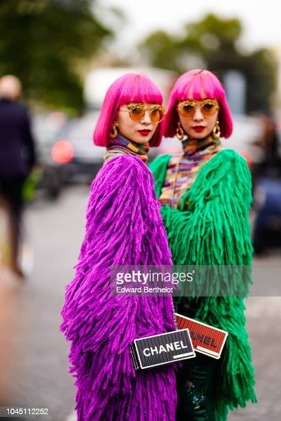 Fashion twins Amiaya wear purple and green faux fur coats and Chanel bags outside Chanel during Paris Fashion Week Womenswear Spring/Summer 2019 on...