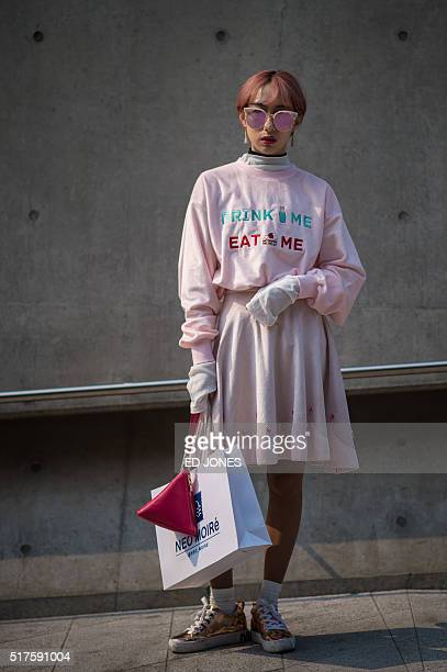 A fashion week attendee poses for a photo at the Dongdaemun Design Plaza during Seoul fashion week on March 26 2016 / AFP / Ed Jones