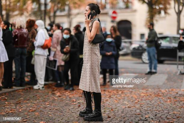Fashion Week Guest wearing a beige dress with details and black boots outside Miu Miu Show on October 05, 2021 in Paris, France.