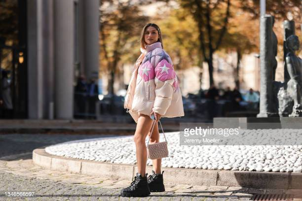 Fashion Week Guest wearing a beige, rose and purple jacket with stars on it and a hotpan and black boots outside Miu Miu Show on October 05, 2021 in...