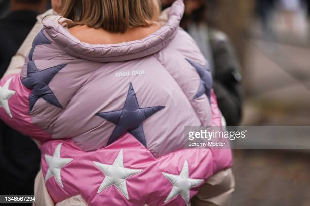 Fashion Week Guest wearing a beige, rose and purple jacket with stars on it outside Miu Miu Show on October 05, 2021 in Paris, France.