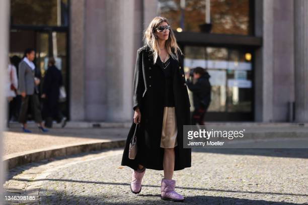 Fashion Week Guest wearing a black cardigan and shirt, beige pants and pink boots outside Miu Miu Show on October 05, 2021 in Paris, France.
