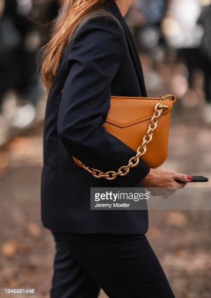 Fashion Week Guest wearing a black suit and a brown bag outside Miu Miu Show on October 05, 2021 in Paris, France.